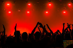 Silhouettes of people in a bright in the pop rock concert in front of the stage. Hands with gesture Horns. That rocks. Party in a Stock Images