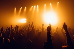 Silhouettes of concert crowd in front of bright stage lights. Unrecognized people in crowd. Copy space background. Crowd of fans a stock images