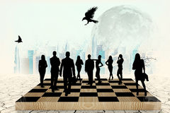 Silhouettes of people on the chess-board Stock Photo