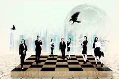 Silhouettes of people on the chess-board Stock Images