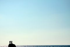 Silhouettes of people on a cliff above the sea Stock Image
