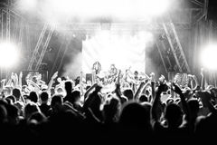 Silhouettes of people at a concert in front of the scene in bright light. Black and White. Picture Stock Photography