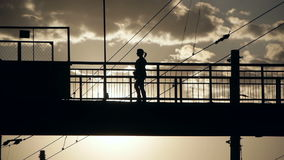 Silhouettes of people crossing railway on the old steel bridge. In the evening stock video
