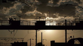 Silhouettes of people crossing railway on the old steel bridge. In the evening stock footage