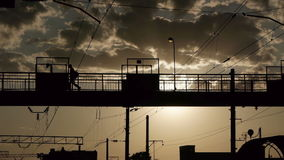Silhouettes of people crossing railway on the old steel bridge. In the evening stock video footage