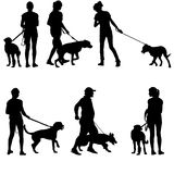 Silhouettes of people and dogs. Royalty Free Stock Images