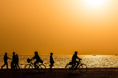 Silhouettes of people enjoying a walk by the seaside of the town. During sunset Royalty Free Stock Photo