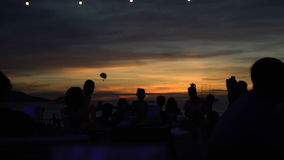 Silhouettes of people hanging out at the beach club during beautiful sunset stock video