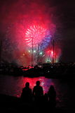Silhouettes of people at harbor by fireworks Stock Photography