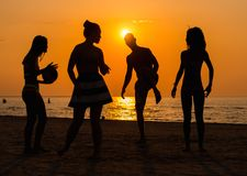 Silhouettes of a people having fun on a beach Stock Photos