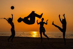 Silhouettes of a people having fun on a beach. Silhouettes a young people having fun on a beach against sunset
