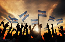 Silhouettes of People Holding Flag of Argentina Stock Images