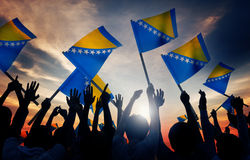 Silhouettes of People Holding Flag of Bosnia and H Stock Photo