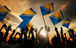 Silhouettes of People Holding Flag of Bosnia and Hercegovina Stock Photo