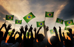 Silhouettes of People Holding the Flag of Brazil Royalty Free Stock Images