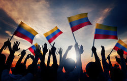 Silhouettes of People Holding Flag of Colombia Stock Image
