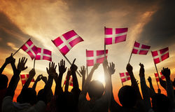 Silhouettes of People Holding the Flag of Denmark Stock Images
