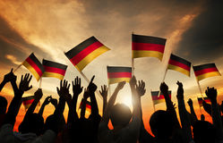 Silhouettes of People Holding Flag of Germany Stock Photos