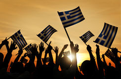 Silhouettes of People Holding Flag of Greece Royalty Free Stock Photos