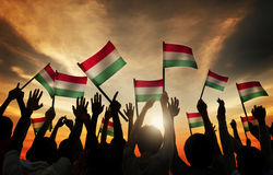 Silhouettes of People Holding the Flag of Hungary Stock Photo