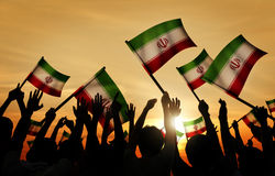 Silhouettes of People Holding Flag of Iran Stock Photo