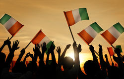 Silhouettes of People Holding Flag of Ireland Stock Photo