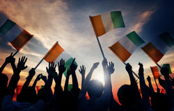 Silhouettes of People Holding Flag of Ireland Stock Photography