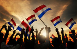 Silhouettes of People Holding Flag of Netherlands Stock Images