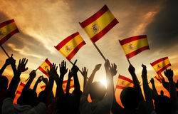 Silhouettes of People Holding Flag of Spain Stock Image