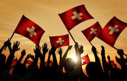 Silhouettes of People Holding Flag of Switzerland Royalty Free Stock Photos