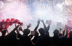 Silhouettes of people holding the Flag of the USA. Royalty Free Stock Photography