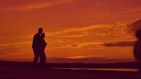 Silhouettes of people hugging slow motion video. Dark silhouettes of women and men embracing on the beach in the evening slow motion video stock video footage