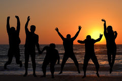 Silhouettes of people jumping Royalty Free Stock Images