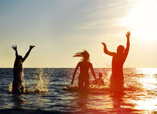 Silhouettes of people jumping in ocean. Silhouettes of young group of people jumping in ocean at sunset Royalty Free Stock Image