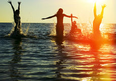 Silhouettes of people jumping in ocean. Silhouettes of young group of people jumping in ocean at sunset Royalty Free Stock Photos