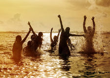 Silhouettes of people jumping in ocean. Silhouettes of young group of people jumping in ocean at sunset Royalty Free Stock Photography