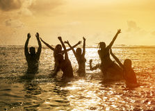 Silhouettes of people jumping in ocean. Silhouettes of young group of people jumping in ocean at sunset Stock Image
