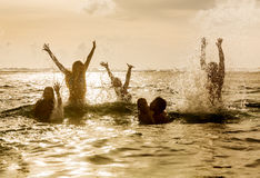 Silhouettes of people jumping in ocean Stock Photos