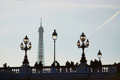 Silhouettes of people and lanterns on the famous Alexandre III bridge and the Eiffel tower. Scenic cityscape of Paris with silhouettes of people and lanterns on Royalty Free Stock Photo