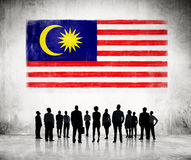 Silhouettes of People Looking at the Malaysian Flag. Silhouettes of Business People Looking at the Malaysian Flag Royalty Free Stock Photos