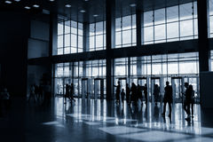 Silhouettes of people in modern hall Stock Images