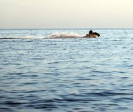 Silhouettes of people in motion on jetski Stock Images
