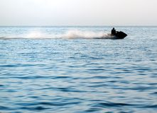 Silhouettes of people in motion on jetski royalty free stock photos