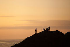 Silhouettes of people on the mountain towering above the sea at night. Silhouettes of people on the mountain towering above the sea at night Stock Image