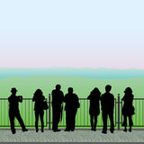 Silhouettes of people on the observation deck. Silhouettes of people standing on the observation deck and looking at the mountains, vector illustration Royalty Free Stock Photo