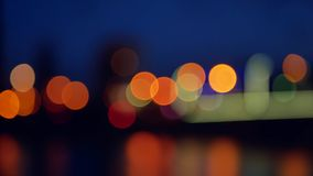 Silhouettes of people in the Park, on the background of night city. The bokeh effect, defocus. Silhouettes of people in the Park, on the background of night stock video