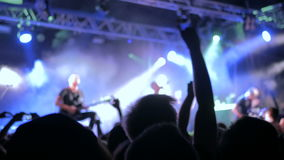 Silhouettes of people partying at rock concert in front of the stage. stock video footage