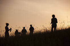 Silhouettes of People picking flowers during midsummer soltice Royalty Free Stock Photography