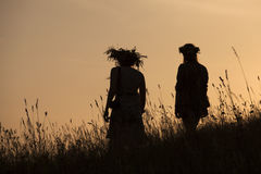 Silhouettes of People picking flowers during midsummer soltice. Celebraton against the background of sunset Stock Image
