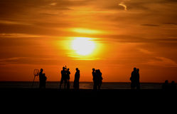 Silhouettes of people on pier. People silhouetted on a pier at sunset Stock Photos